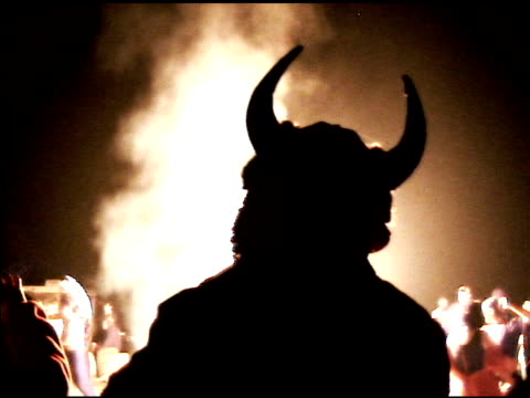 Man With Horns watching Flame Bursts at Night