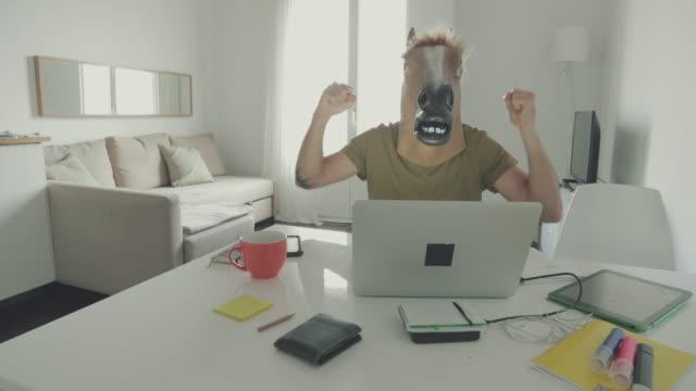 vidéos et rushes de homme avec cheval masque travaillant à la maison - cheval