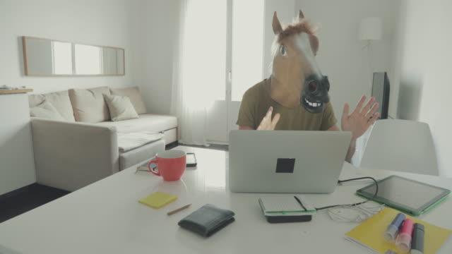 vídeos y material grabado en eventos de stock de hombre con caballo cabeza máscara trabajando en casa - caballo familia del caballo