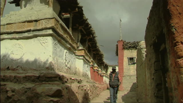 stockvideo's en b-roll-footage met ms td man with horse walking on dirt road along mud buildings / lo manthang, mustang, nepal - baseballpet