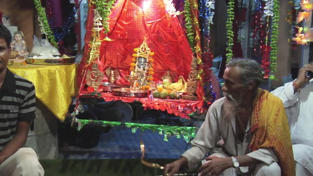 ms zi man with idol of lord krishna in temple on eve of janmashtami / delhi, india - lametta stock-videos und b-roll-filmmaterial