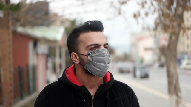 man with in coronavirus infected city wearing a surgical mask - silver coloured stock videos & royalty-free footage