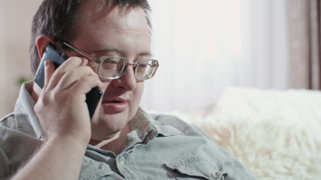man with intellectual disability talking on mobile phone - intellectual disability stock videos & royalty-free footage