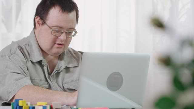 man with intellectual disability working on laptop - intellectual disability stock videos & royalty-free footage