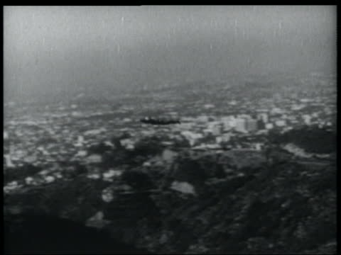 b/w 1952 pan man with jet pack flying over hills with city in background - 1952 stock videos & royalty-free footage