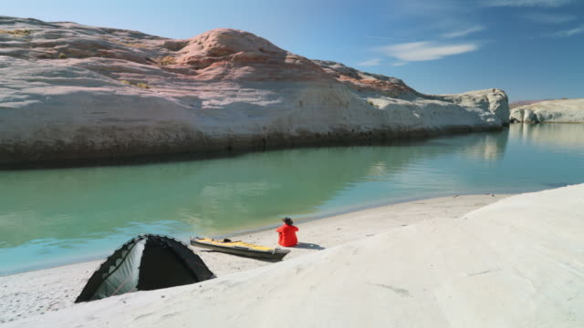ws man with kayak camps at lake powell - lago powell video stock e b–roll