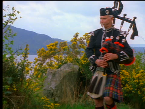 man with kilt playing bagpipes marching off screen / loch ness in background / inverness, scotland - スコットランド点の映像素材/bロール