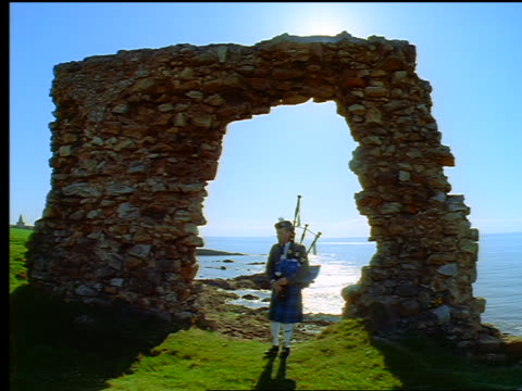 man with kilt playing bagpipes under arch of castle ruins / ocean in background / newark castle, scotland - kilt stock videos & royalty-free footage