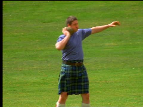 vídeos de stock, filmes e b-roll de man with kilt throwing rock in grassy field / scotland - braço humano