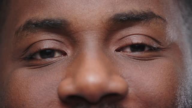vídeos de stock e filmes b-roll de man with kind brown eyes smiles gently looking into camera - afro americano