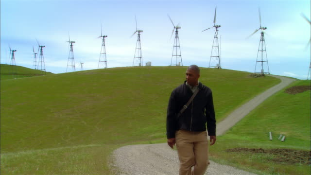 ms ds pan man with laptop bag walking on gravel road away from wind turbines on hillside / livermore, california, usa - laptop bag stock videos and b-roll footage