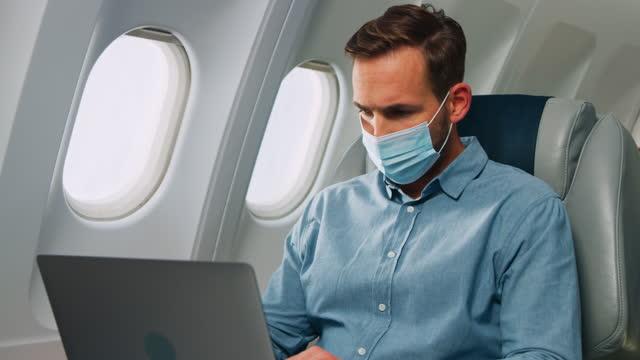 mann mit laptop im flugzeug - flugpassagier stock-videos und b-roll-filmmaterial