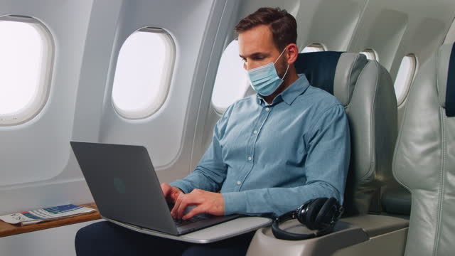man with laptop in airplane - business travel stock videos & royalty-free footage