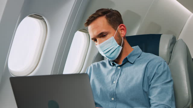 vidéos et rushes de homme avec l'ordinateur portatif dans l'avion - voyage d'affaires