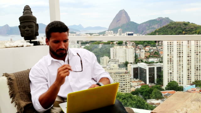 Man with laptop on balcony