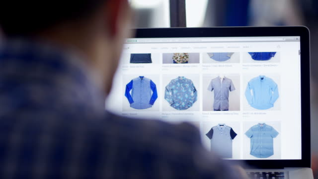 vidéos et rushes de man with laptop scrolls through online clothing store, looks at short sleeve shirt - acheter