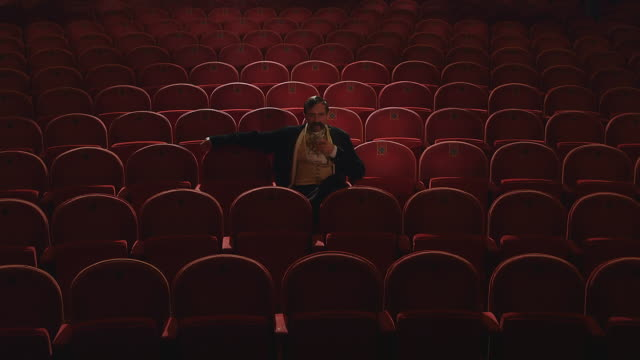 vidéos et rushes de  ms man with large mustache drinking while sitting in empty opera theater and walking / united kingdom - moustache