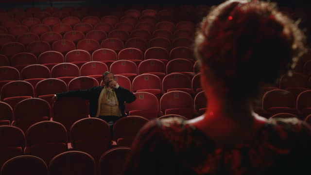 ms r/f man with large mustache drinking while sitting in empty opera theater and watching woman on stage singing / united kingdom - bühne stock-videos und b-roll-filmmaterial