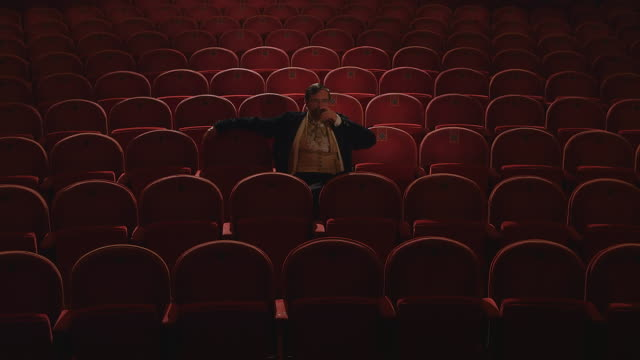 ms man with large mustache sitting in empty opera theater / united kingdom - オペラ座点の映像素材/bロール