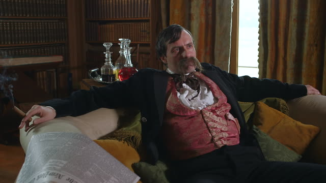 MS Man with large mustache sitting on couch with newspaper and smoking / United Kingdom