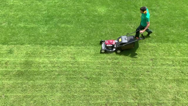 man with lawn mower cutting the grass in lugano, switzerland. - tagliaerba video stock e b–roll