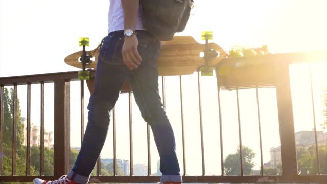 vídeos y material grabado en eventos de stock de hombre con longboard a - mochila bolsa