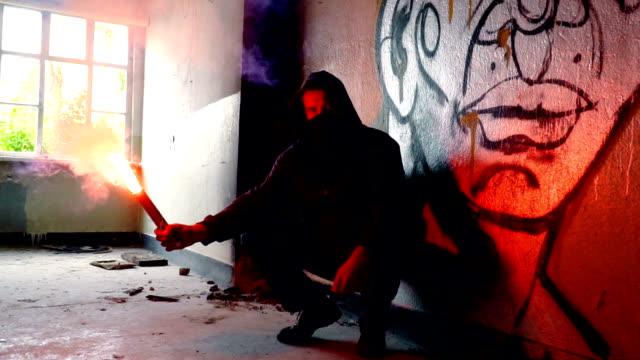 フレアを持ちながらしゃがむマスクとパーカーを持つ男 - 公共物破壊点の映像素材/bロール