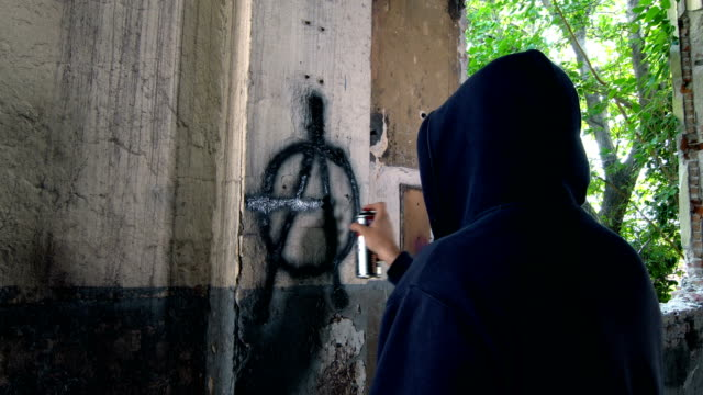 man with mask and hoodie doing graffiti - anarchy symbol - protestor stock videos & royalty-free footage