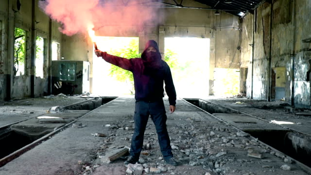 man with mask and hoodie holding flare - terrorismo video stock e b–roll