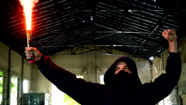 man with mask and hoodie holding flare with fist in the air - youth culture stock videos & royalty-free footage
