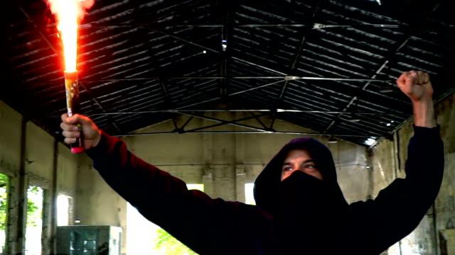 空中で拳でフレアを保持するマスクとパーカーを持つ男 - 公共物破壊点の映像素材/bロール