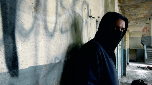 man with mask and hoodie looking at the camera - terrorismo video stock e b–roll
