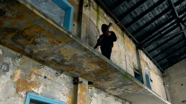 vídeos de stock e filmes b-roll de man with mask and hoodie walking with a plank in his hands - low angle view - bandido
