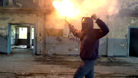 man with mask and hoodie walking with flare in his hand - violence stock videos & royalty-free footage
