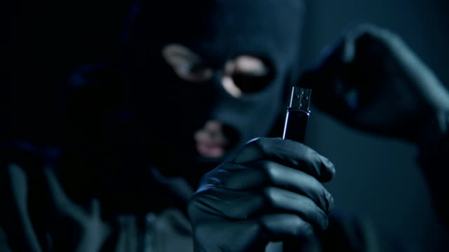 man with mask looking usb flash drive - burglar stock videos & royalty-free footage