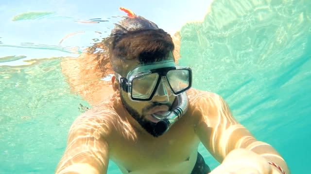Man with mask swimming underwater in tropical sea
