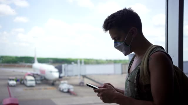 man with mask using cellphone - airport stock videos & royalty-free footage