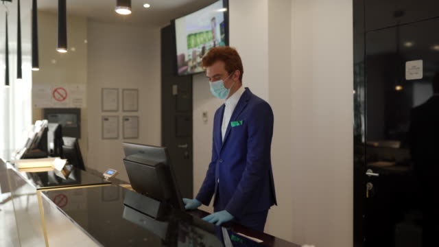 man with medical mask working in hotel at the reception - checkout stock videos & royalty-free footage