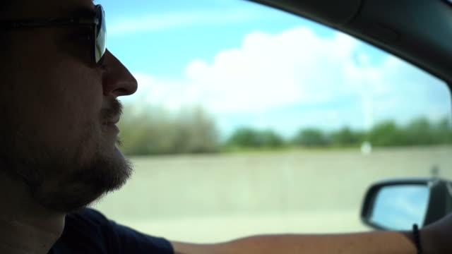 vidéos et rushes de homme avec barbe malpropre et lunettes de soleil au volant de voiture - dedans