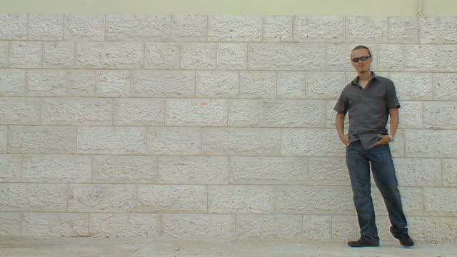 mann mit handy in der nähe der white brick wall - ziegelmauer stock-videos und b-roll-filmmaterial