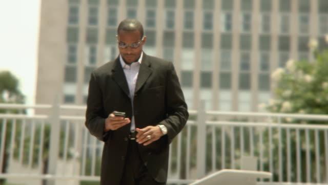 ms man with mobile phone walking towards camera, jacksonville, florida, usa - ゴーティー点の映像素材/bロール