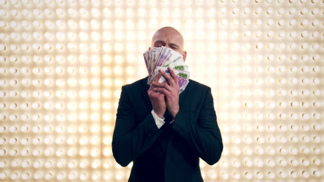 man with money in front of lightwall - euro symbol stock videos and b-roll footage