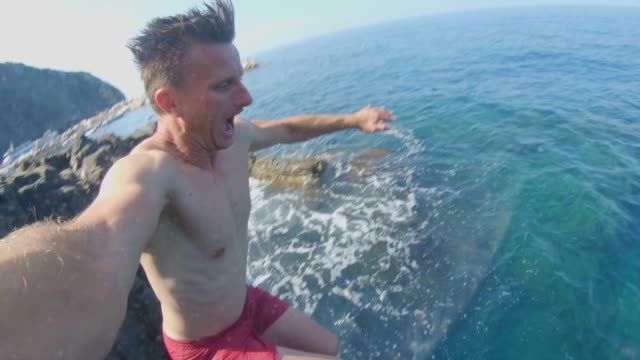 ms man with monopod jumping into sunny sea - real time stock videos & royalty-free footage