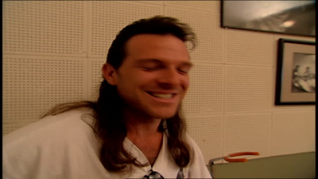 man with mullet playing a guitar with dollar bill on neck at sun studio - tennessee stock-videos und b-roll-filmmaterial