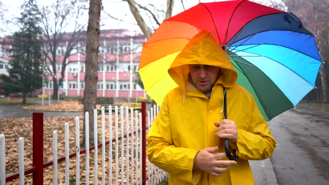 man with multi colored umbrella walking alone - warm clothing stock videos and b-roll footage