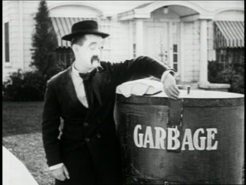 """b/w 1923 man with mustache (snub pollard) covering """"garbage"""" sign to make it """"garage"""" on container - 1923 stock videos & royalty-free footage"""