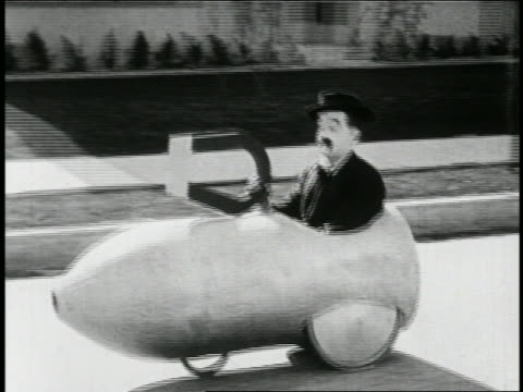B/W 1923 man with mustache (Snub Pollard) in mini-car with giant magnet being pulled on street / feature