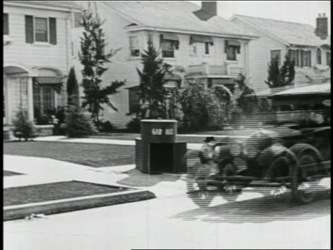 b/w 1923 man with mustache (snub pollard) in mini-car with giant magnet following passing car / feature - 1923 stock videos & royalty-free footage