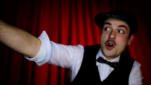 Man with mustache shouting in front of a theater curtain