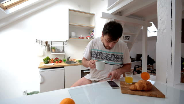man with no pants having a morning routine with coffee and smartphone - men's underpants stock videos and b-roll footage